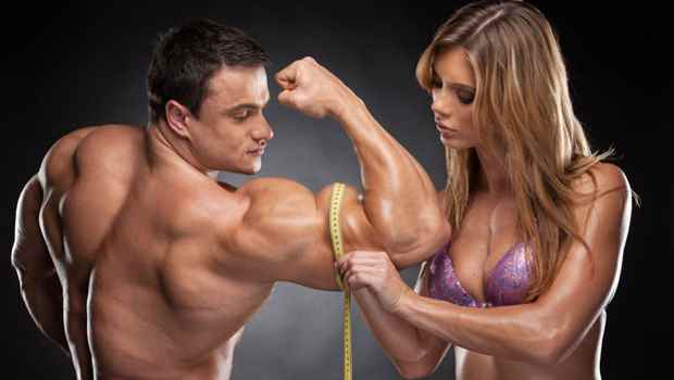 Sexy fit blond woman measure hand male  muscular. Standing together isolated over black background